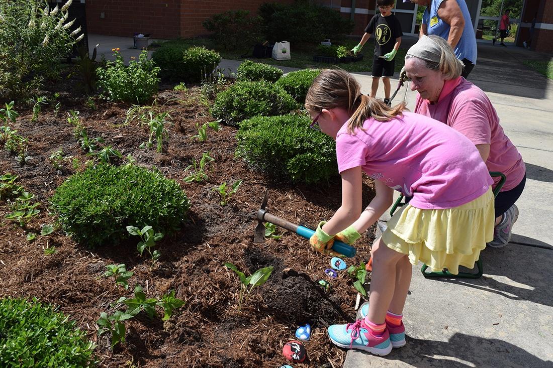 student and volunteer gardening